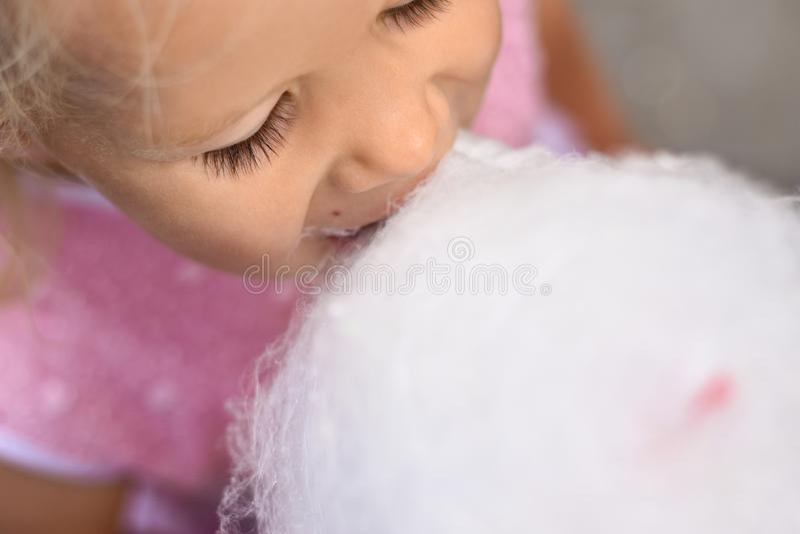 Dziewczyna w różowej sukni je białego bawełnianego cukierek, odgórny widok obraz royalty free