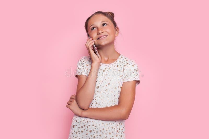 Dziewczyna w różowej sukni, nastolatek opowiada na telefonie komórkowym na różowym tle zdjęcia royalty free