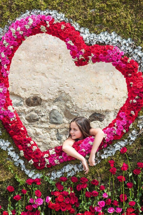 Dziewczyna w ramie róże na tle serce zdjęcie stock