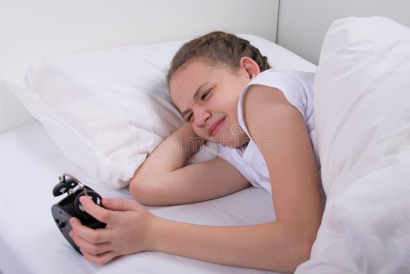 dziewczyna w ranku w łóżku, przedstawienie emocje, patrzeje budzika zdjęcia stock