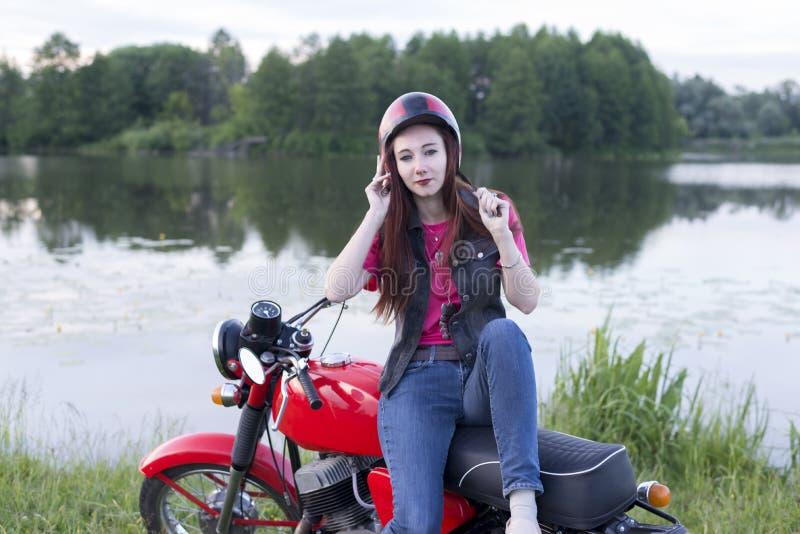 Dziewczyna w retro hełma obsiadaniu na rocznika motocyklu outdoors zdjęcia royalty free