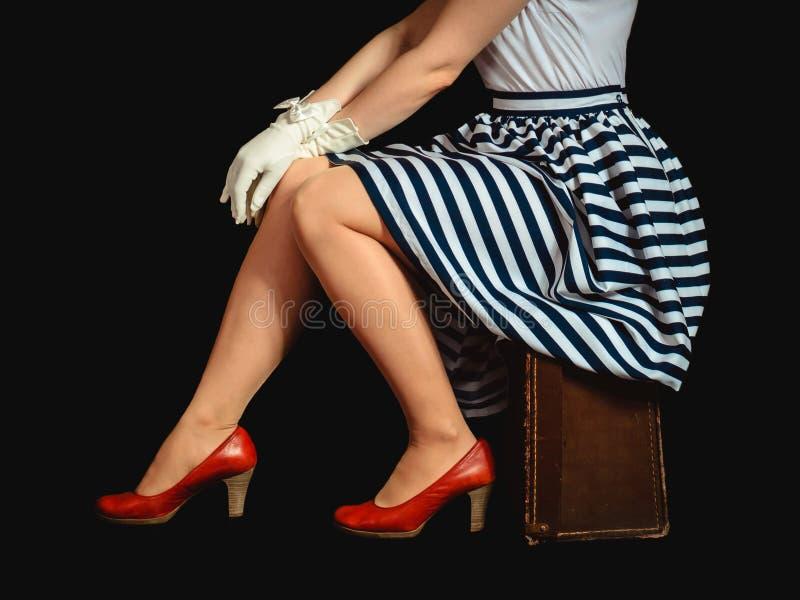 Dziewczyna w retro stylu siedzi na walizce na czarnym tle zdjęcia stock