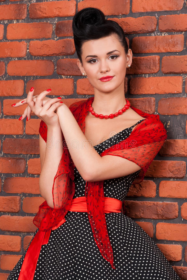 Dziewczyna w rocznik sukni blisko ściana z cegieł fotografia royalty free