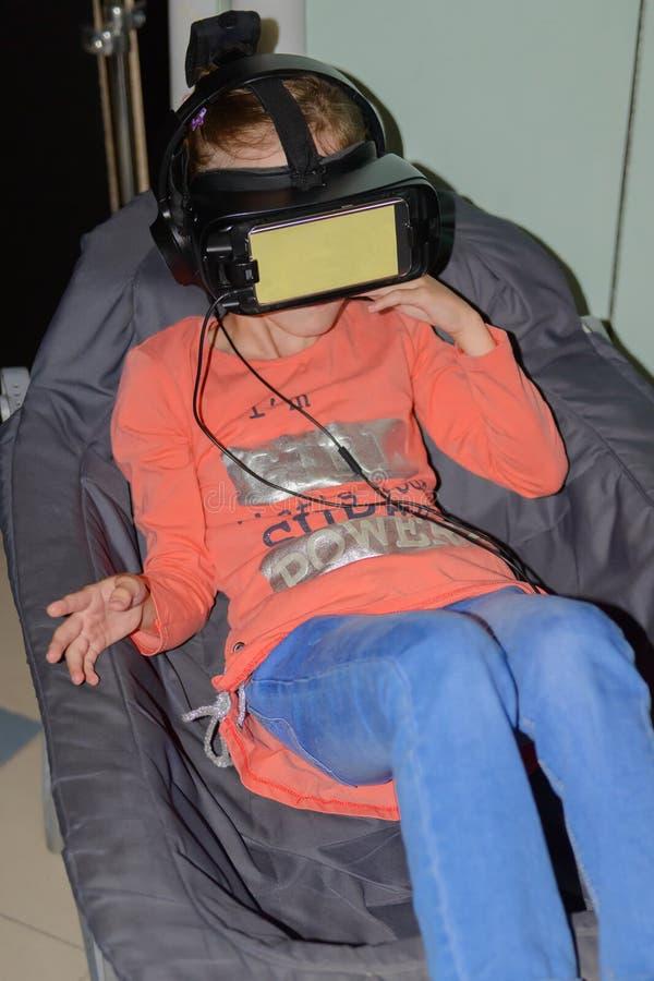 Dziewczyna w rzeczywistość wirtualna szkłach siedzi zdjęcie stock