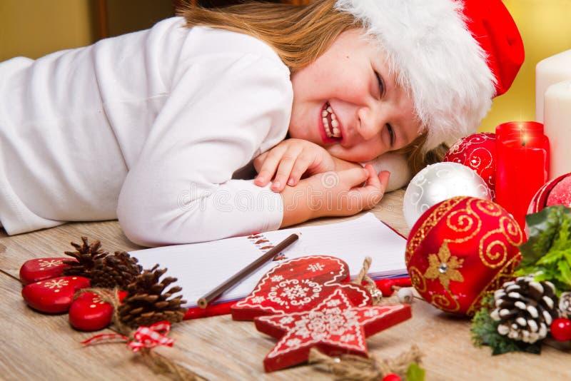 dziewczyna w Santa kapeluszu pisze liście Santa blisko bożych narodzeń de zdjęcie royalty free