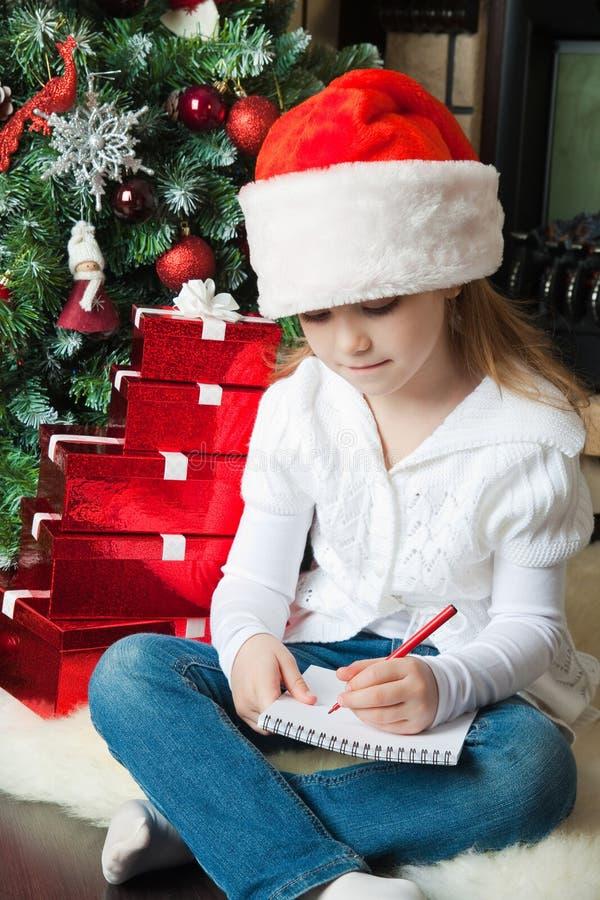 Dziewczyna w Santa kapeluszu siedzi list i pisze Santa obrazy royalty free