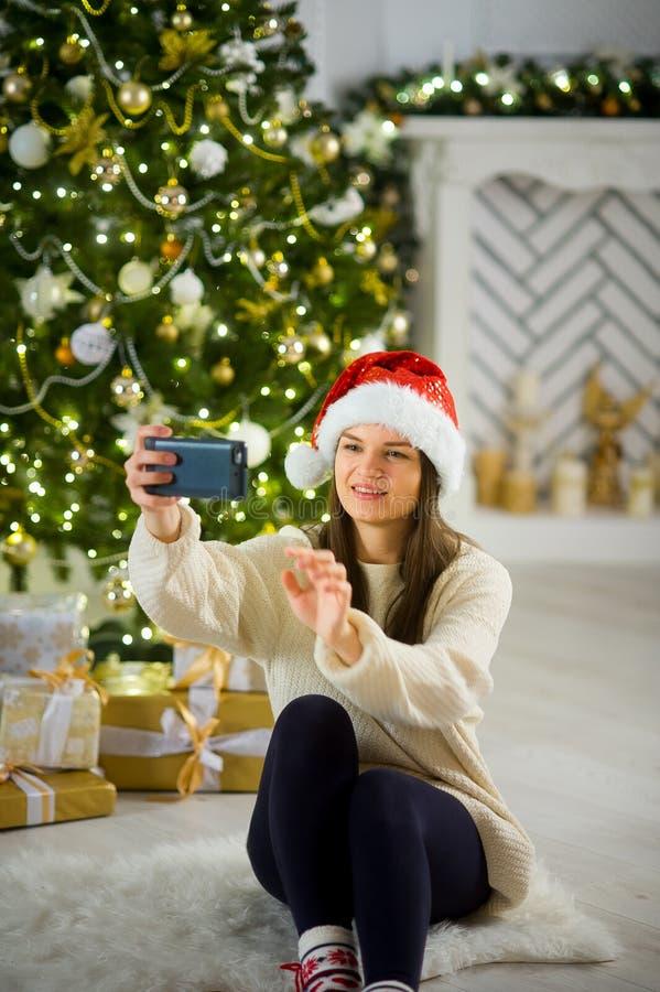 Dziewczyna w Santa ` s nakrętce robi selfie przeciw tłu choinka zdjęcia royalty free