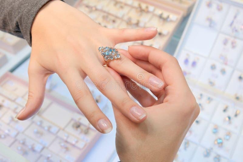Dziewczyna w sklepie jubilerskim próbuje dalej jej palec złocisty pierścionek z diamentami na tle sklepowy okno Kupienie i zakupy zdjęcia stock
