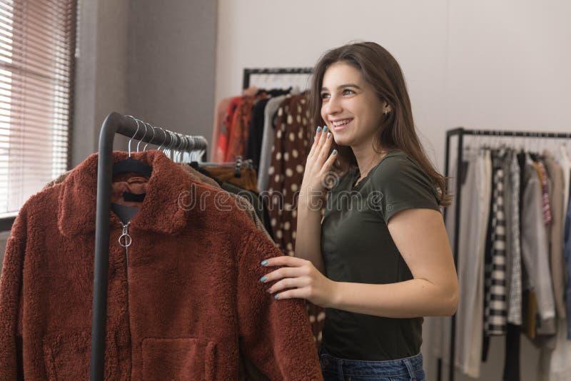 Dziewczyna w sklepie odzieżowym wybiera nowego futerkowego żakiet zdjęcia stock