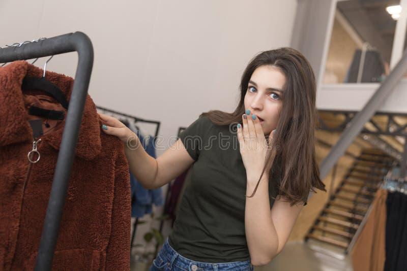 Dziewczyna w sklepie odzieżowym wybiera nowego futerkowego żakiet fotografia royalty free
