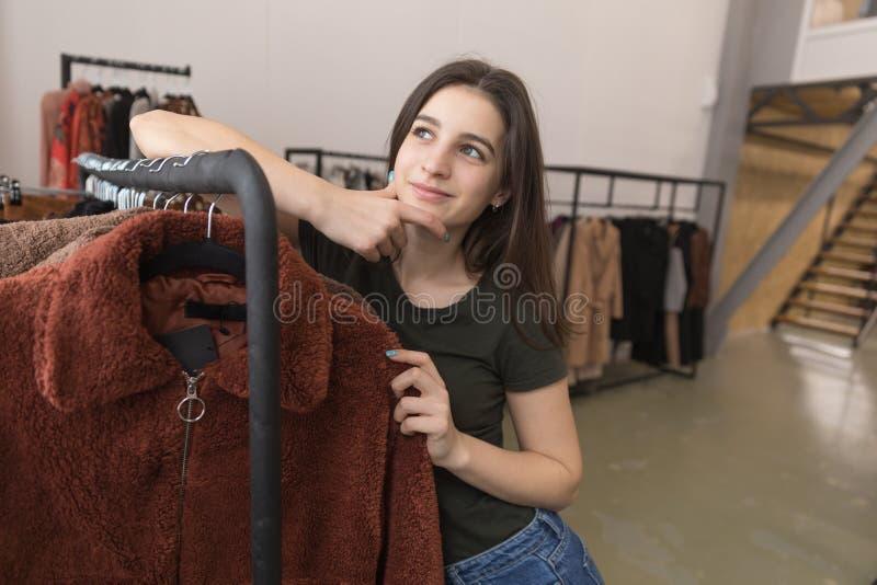 Dziewczyna w sklepie odzieżowym wybiera nowego futerkowego żakiet zdjęcie royalty free