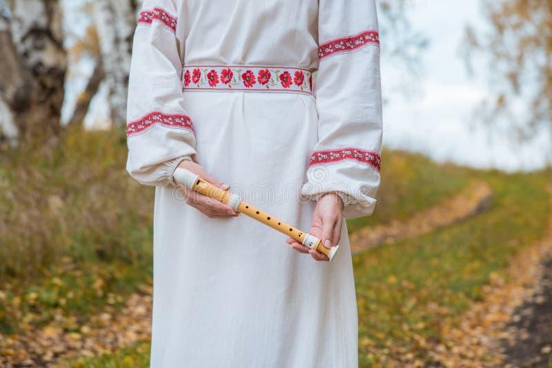 Dziewczyna w Slawistycznych suknia chwytach w jej rękach flet w a zdjęcie royalty free