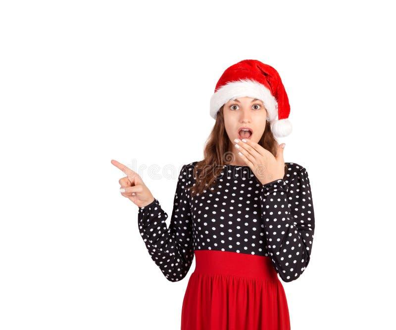 Dziewczyna w smokingowej niespodziance pokazuje produkt emocjonalna dziewczyna w Santa Claus bożych narodzeń kapeluszu odizolowyw obraz stock