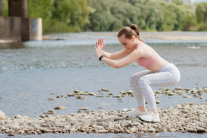 Dziewczyna w sportów mundurach robi rozciągliwości na brzeg rzekim zdjęcie royalty free
