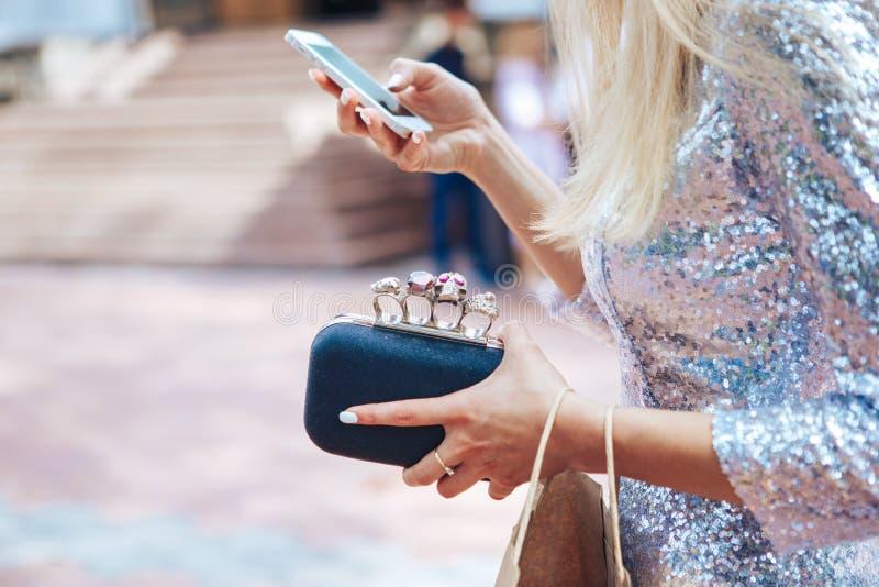 Dziewczyna w srebnej sukni z małej czarnej torebki mosiężnymi knykciami Mod odzieżowi akcesoria ustawiający Mosiężni knykcie zdjęcie stock