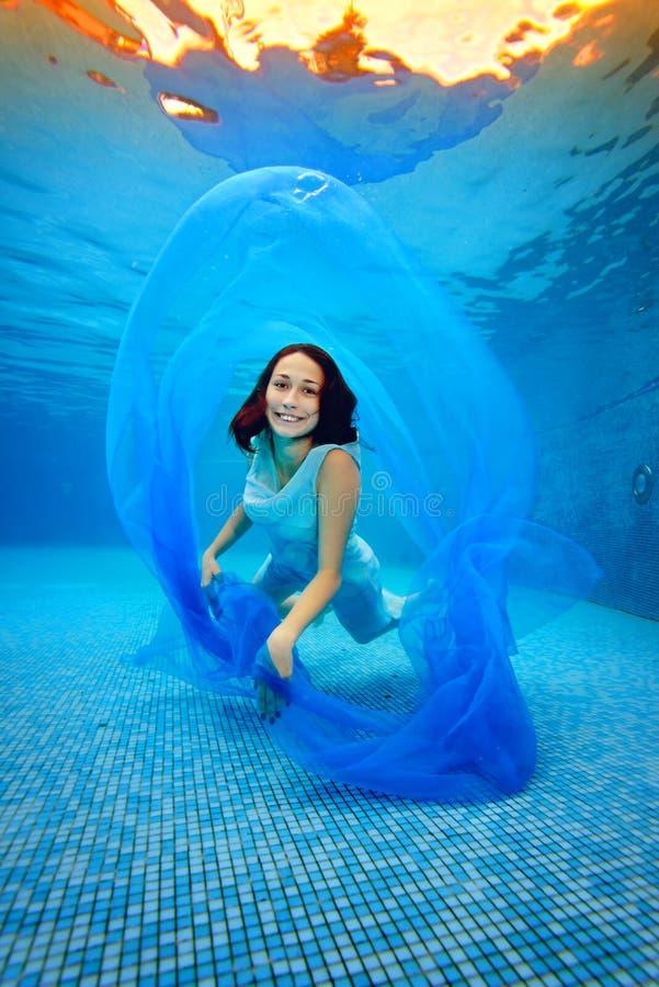 Dziewczyna w sukni pozować podwodny przy dnem basen, bawić się z błękitnym płótnem, patrzejący ono uśmiecha się i kamerę zdjęcia stock