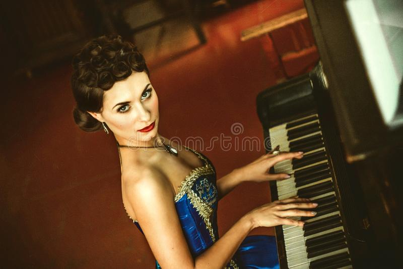 Dziewczyna w sukni przy pianinem zdjęcie stock