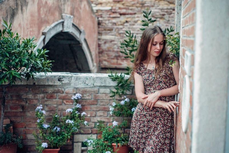 Dziewczyna w sukni spaceruje wygodnym starym podwórzem zdjęcia royalty free