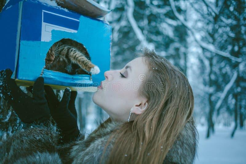 Dziewczyna w szarym żakiecie i figlarce która dotyka jej łapę od birdhouse zdjęcie stock