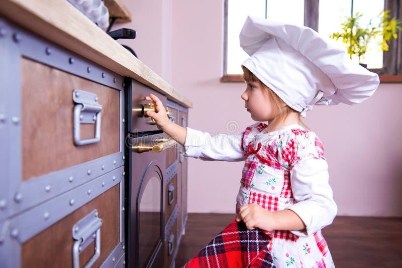 Dziewczyna w szefa kuchni kapeluszu stawia piernikowych ciastka w piekarniku zdjęcia royalty free