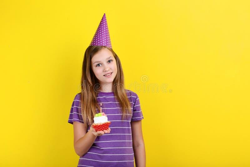 Dziewczyna w urodzinowej kapeluszowej mienie babeczce fotografia royalty free