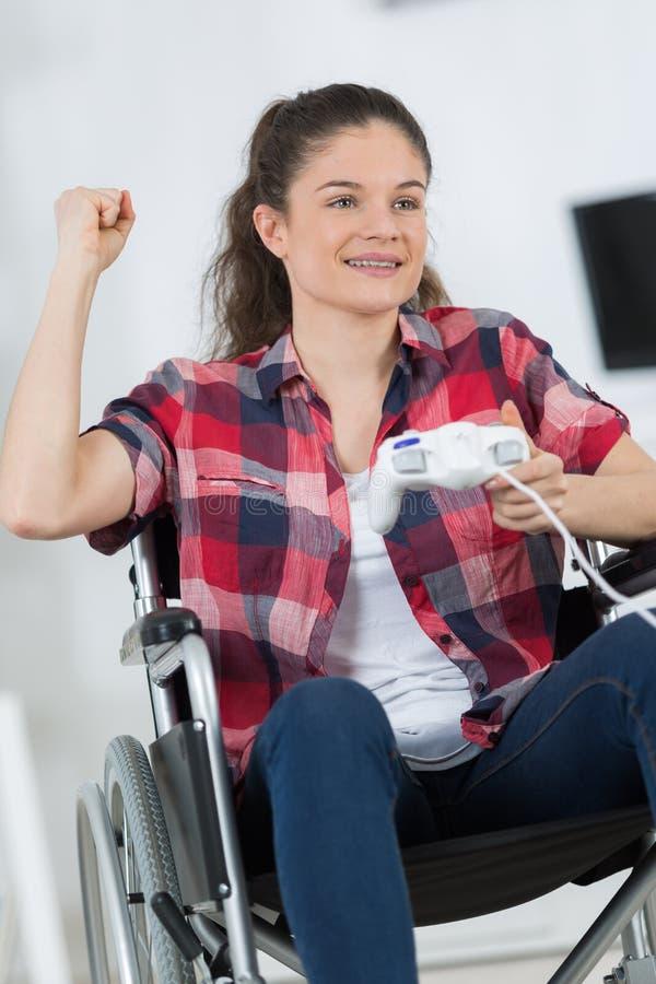 Dziewczyna w wózku inwalidzkim bawić się wideo gry obrazy royalty free