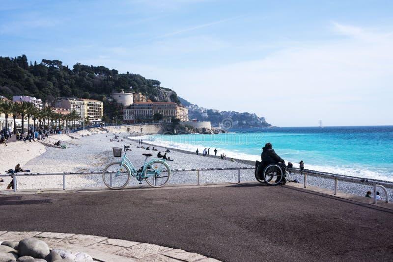 dziewczyna w wózku inwalidzkim siedzi na brzeg lazurowy morze Piękny błękitny morze, parkujący rower, góry w mgiełce i statek, ja zdjęcia royalty free