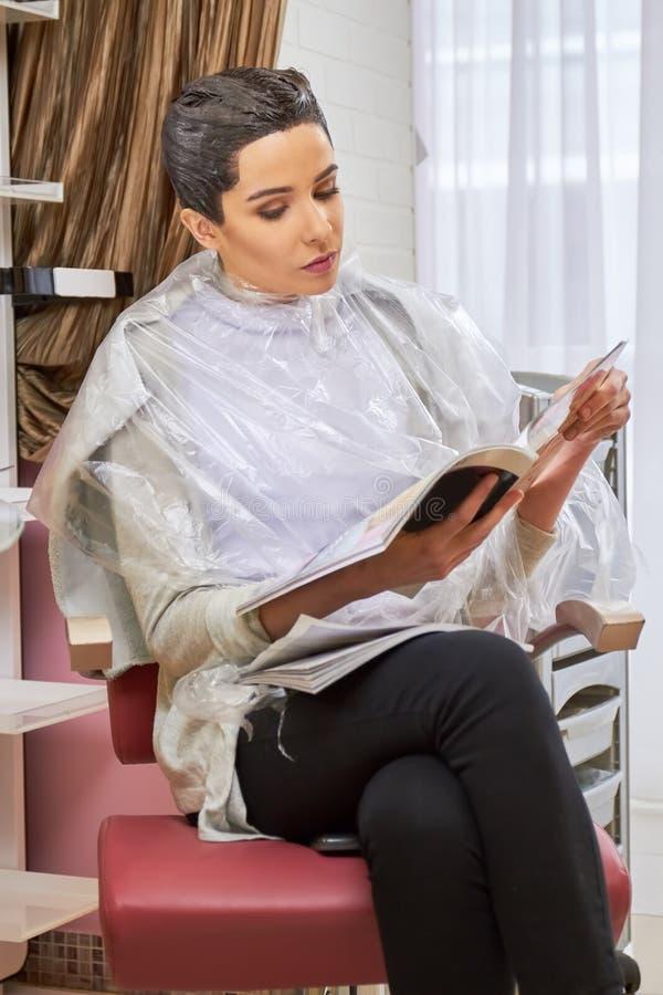 Dziewczyna w włosianego salonu czytaniu zdjęcie royalty free