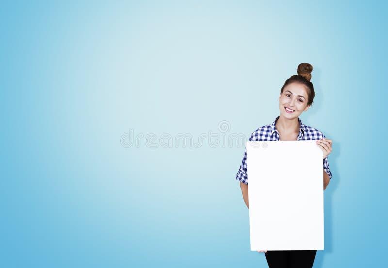 Dziewczyna w w kratkę koszula z plakatową pobliską błękit ścianą obraz royalty free