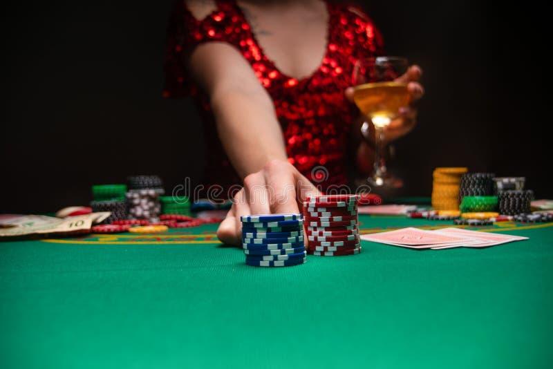 Dziewczyna w wieczornej czerwonej sukience gra w kasynie, podnosząc stosy za pomocą chipów do kur Kasyna dla graczy, kluby nocne zdjęcie royalty free