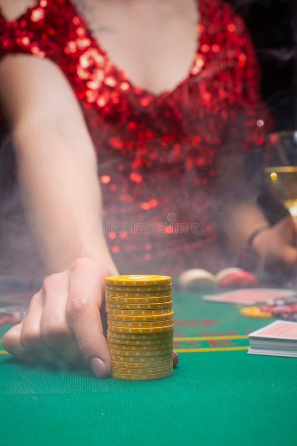 Dziewczyna w wieczornej czerwonej sukience gra w kasynie, podnosząc stosy za pomocą chipów do kur Kasyna dla graczy, kluby nocne fotografia royalty free