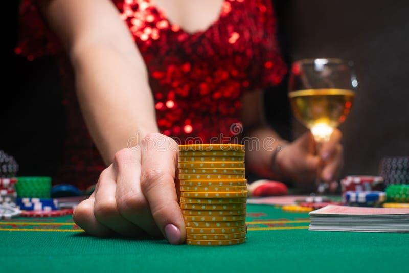 Dziewczyna w wieczornej czerwonej sukience gra w kasynie, podnosząc stosy za pomocą chipów do kur Kasyna dla graczy, kluby nocne fotografia stock