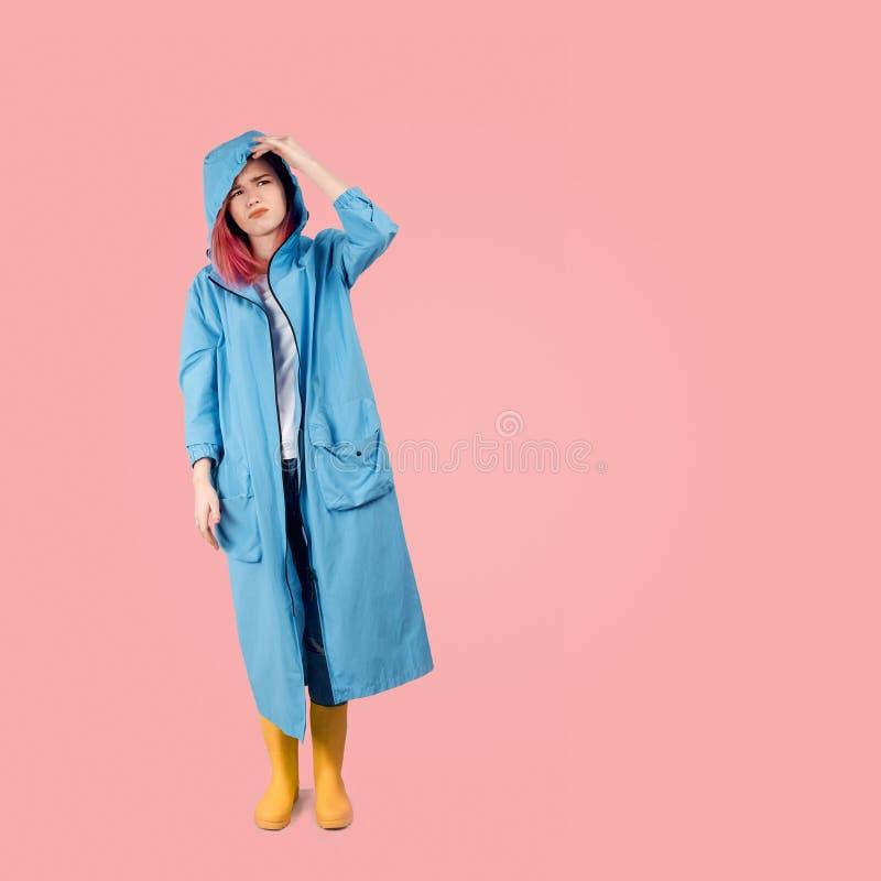 Dziewczyna w wiosna dowodu odzieży marszczy brwi kapiszon przyglądającego w górę i podnosi udaremnia złą pogodą fotografia stock