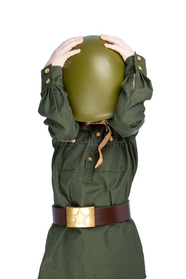 Dziewczyna w wojskowym uniformu, zakrywającym jej twarz z hełmem na białym tle, zdjęcie royalty free