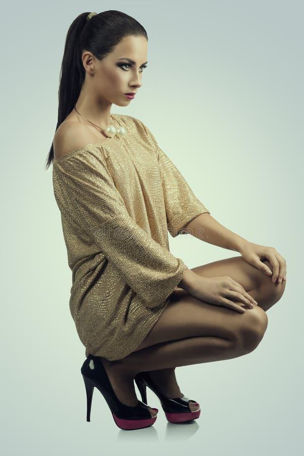 Dziewczyna w złoto sukni patrzeje prosto naprzód zdjęcie stock