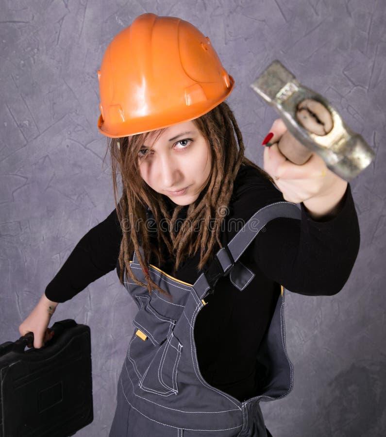 Dziewczyna w zbawczego hełma kamizelki mienia młota pomarańczowym narzędziu zdjęcia royalty free