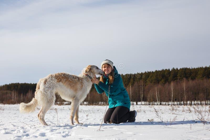 Dziewczyna w zielonej narciarskiej kurtce na jej kolanach i Rosyjski biały ogar w śnieżnym polu w pogodnej zimie zdjęcie royalty free