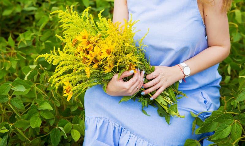 Dziewczyna w zielonym polu siedzi z bukietem dzicy kwiaty obrazy stock