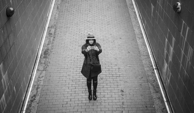 Dziewczyna w zimy odzieżowej strzelaninie na smartphone, dzień, plenerowy zdjęcie royalty free