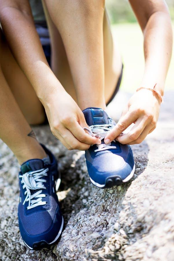 Dziewczyna wiąże ona buty obraz stock