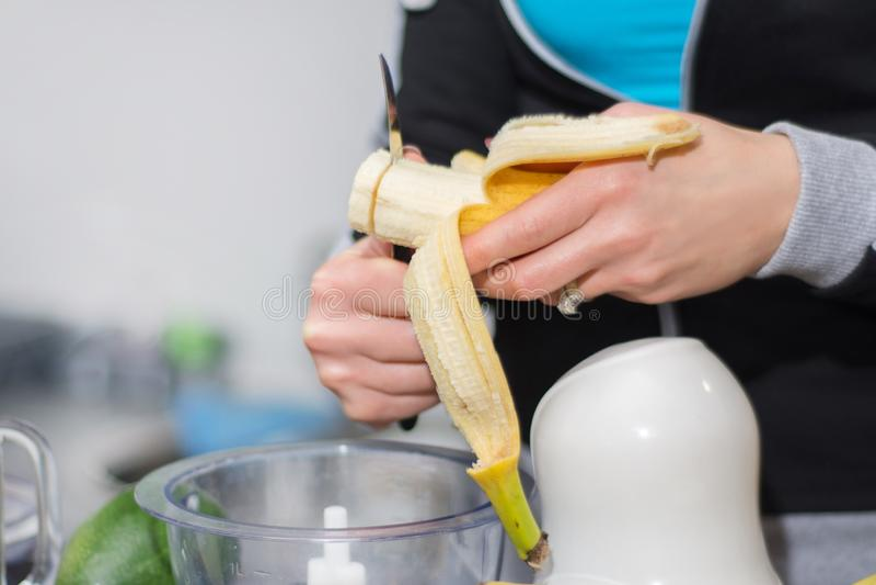 Dziewczyna wręcza cięcia i narządzanie banana dla smoothie obraz royalty free