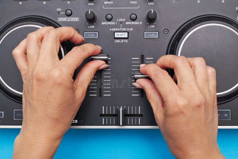 Dziewczyna wręcza działanie z DJ melanżerem na błękitnym tle obraz royalty free