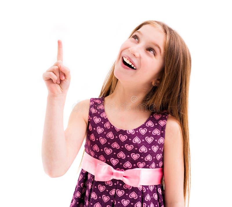 Dziewczyna wskazuje up, będący ubranym deseniującą fiołek suknię zdjęcie royalty free