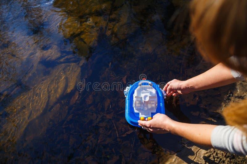 Dziewczyna wszczyna zabawkarską łódź w lasowej zatoczce obraz stock