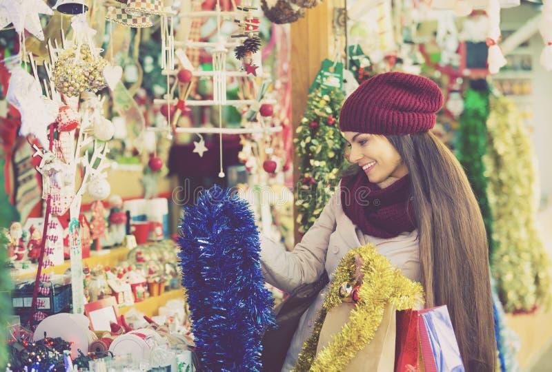 Dziewczyna wybiera Bożenarodzeniową dekorację przy rynkiem zdjęcie royalty free