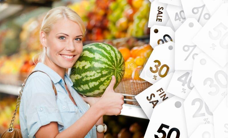 Dziewczyna wybiera owoc przy sklepem wręcza arbuza na sprzedaży zdjęcia royalty free