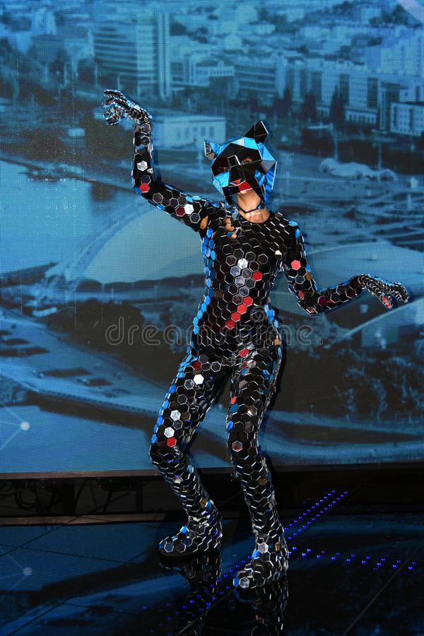 Dziewczyna wykonuje w arenie z nikłą postacią w fantastycznym lustrzanym kostiumu z maską lustra fotografia stock