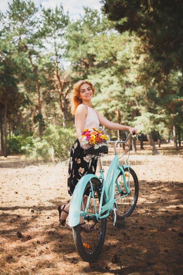 Dziewczyna wziąć jej rower dla spaceru w jesieni jesieni lasowym Pięknym dniu w lesie z kwiatami zdjęcie royalty free