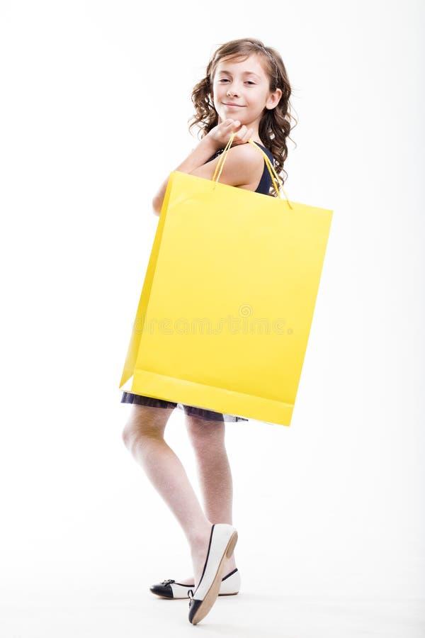 Dziewczyna z żółtym torba na zakupy portretem na bielu fotografia royalty free