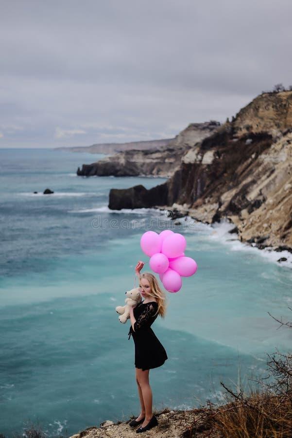Dziewczyna z balonami przeciw tłu burzowy morze, dramat e zdjęcie royalty free